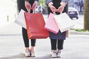 due giovani donne che trasportano borse della spesa mentre camminano per strada dopo aver visitato i negozi foto