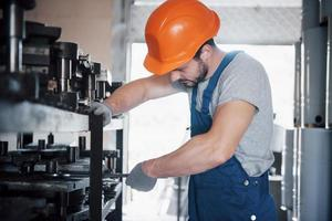 ritratto di un giovane lavoratore con un elmetto in una grande fabbrica di riciclaggio dei rifiuti. l'ingegnere controlla il lavoro di macchine e altre attrezzature foto
