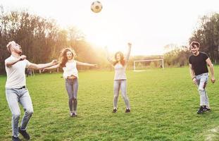 un gruppo di amici in abbigliamento casual gioca a calcio all'aria aperta. le persone si divertono e si divertono. riposo attivo e tramonto panoramico. foto