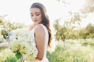 una bella ragazza con un vestito bianco chiaro e un mazzo di fiori estivi depone una bella giornata in giardino foto