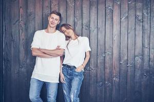 giovane coppia, ragazzo e ragazza insieme su uno sfondo di parete in legno. sono felici insieme e vestiti allo stesso modo. sempre di tendenza foto
