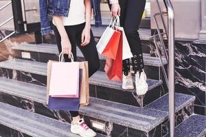 due giovani donne che trasportano le borse della spesa mentre camminano sulle scale dopo aver visitato i negozi foto