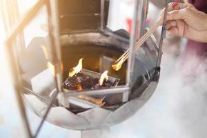 mani dei vecchi, accendi i bastoncini d'incenso dalla lampada a olio nel tempio tailandese. foto