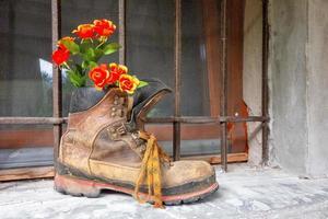 vecchio scarpone da montagna con fiori all'interno sul balcone della finestra foto