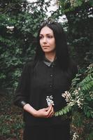 donna in abiti neri e occhiali tiene un fiore bianco su uno sfondo di foglie verdi foto