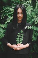 donna in abito nero che tiene un ramoscello in mano sullo sfondo della foresta foto