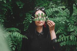 donna in abiti neri e occhiali tiene un ramoscello in mano su uno sfondo di foglie verdi foto
