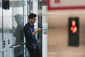 mani di un giovane asiatico, utilizzando un telefono cellulare intelligente, in ascensore foto