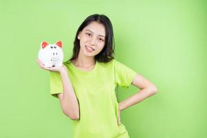 ragazza asiatica che tiene salvadanaio in mano concetto di risparmio di denaro foto