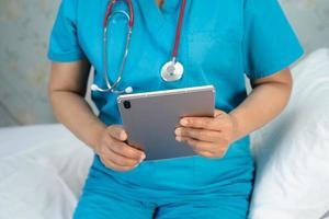 medico in possesso di tablet digitale per cercare dati per curare il paziente nel reparto ospedaliero di cura, concetto medico sano e forte. foto