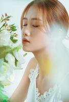 ritratto di bella ragazza asiatica in mano bouquet, isolato su sfondo bianco foto