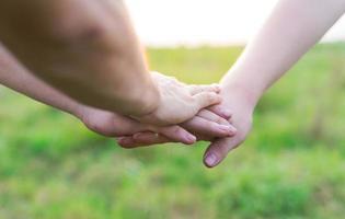 primo piano dei giovani che uniscono le mani. gli amici che si tengono per mano mostrano solidarietà e lavoro di squadra. foto
