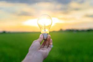 immagine di un uomo che tiene in mano una lampadina foto