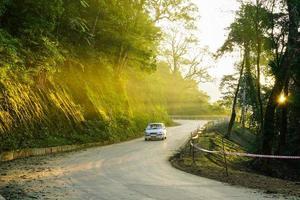 immagine della strada di montagna di ba vi mountain, raggi di sole trafiggono alberi, macchine corrono sulla strada foto