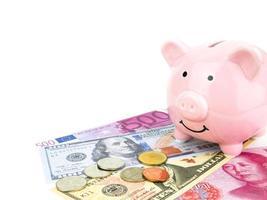 salvadanaio rosa su dollari, cinese, banconota in euro isolato su sfondo bianco, concetto di risparmio foto