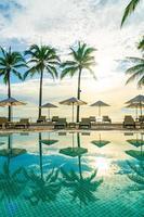 bellissimo ombrellone di lusso e sedia intorno alla piscina all'aperto in hotel e resort con palme da cocco al tramonto o all'alba sky foto
