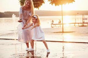 una donna che gioca con un bambino vicino all'oceano nel parco al tramonto foto