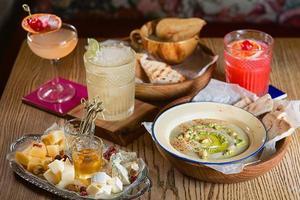 hummus di cibo, gelatina, diversi tipi di formaggio e cocktail alcolici sul tavolo foto