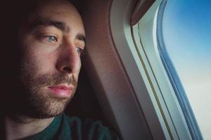 primo piano di un uomo pensieroso che guarda fuori attraverso il finestrino di un aeroplano foto
