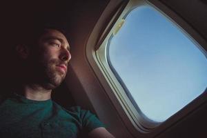 uomo pensieroso che guarda fuori attraverso il finestrino di un aeroplano foto