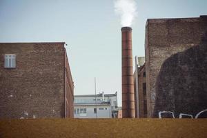 fumo emesso da un camino industriale in mattoni in un vecchio edificio industriale foto