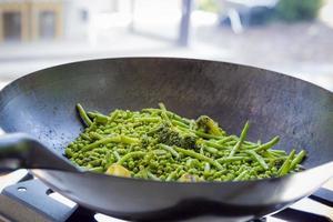 close up su fagiolini, broccoli e piselli vengono cotti in una grande padella di ferro foto