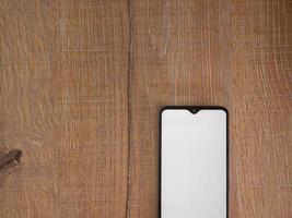 il modello nero dello smartphone mobile si trova sulla superficie con lo schermo in bianco isolato su fondo di legno foto