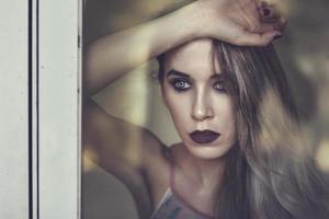 donna premurosa che guarda attraverso la finestra foto