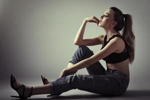 giovane donna che indossa reggiseno nero e jeans blu seduto sul pavimento. girato in studio. foto