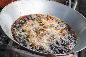 pollo fritto in padella con olio bollente foto
