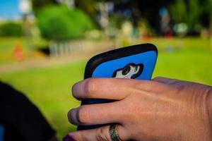 primo piano di una donna che tiene lo smartphone con la mano foto
