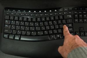 uomo che digita su una tastiera con lettere in ebraico e in inglese foto
