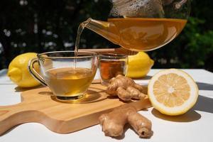 la limonata calda con lo zenzero nella teiera è stata versata nella tazza da tè e servita sul tavolo al bar foto