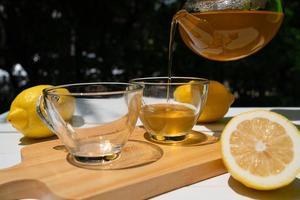 il tè caldo nella teiera è stato versato nella tazza da tè e servito sul tavolo nel bar foto