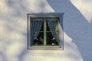 vecchia finestra con cornice verde su un muro di pietra bianca foto