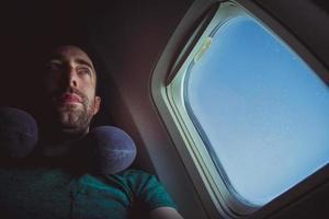 uomo pensieroso con cuscino per il collo vicino al finestrino di un aeroplano foto