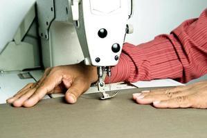 le mani lavorano una macchina da cucire foto