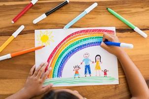 bambino che disegna una famiglia felice foto