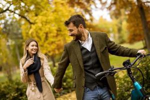 giovane coppia nel parco autunnale con bicicletta elettrica foto