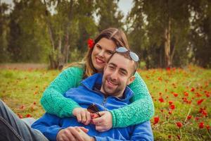 giovane coppia seduta sull'erba in un campo di papaveri rossi e sorride alla telecamera foto