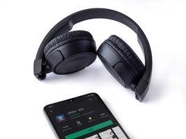 smartphone mobile nero con pagina del play store dell'app galgalatz e cuffie wireless su sfondo bianco foto