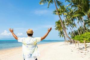 felice giovane asiatico sulla spiaggia tropicale foto