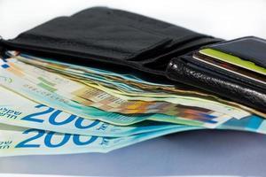 pila di varie banconote in siclo israeliano in un portafoglio aperto in pelle nera foto