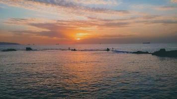 bellissima vista del tramonto sul mare con navi e silhouette di pescatori foto