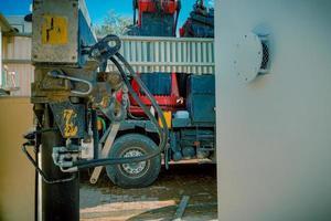 primo piano dei pistoni idraulici di un camion di sartiame di parcheggio con macchina del braccio della gru di sollevamento pesante foto