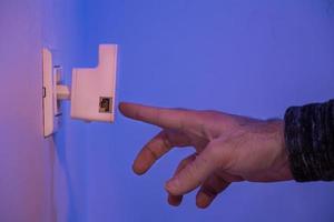 l'uomo preme con il dito sul pulsante wps sul ripetitore wifi che si trova nella presa elettrica a muro foto