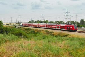 treno passeggeri israeliano rosso in movimento fuori città vicino all'autostrada 4 foto