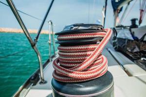 verricello con fune rossa e bianca su barca a vela in mare foto