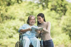 donna felice su una sedia a rotelle che legge un libro con sua figlia al parco foto