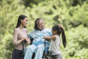 nonna felice in sedia a rotelle con sua figlia e suo nipote in un parco, vita felice tempo felice. foto